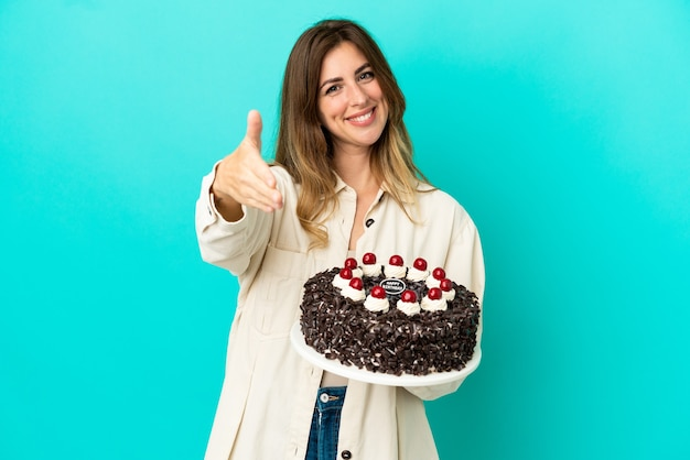 Caucasian woman holding birthday cake isolated on blue background shaking hands for closing a good deal