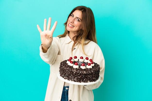 幸せな青い背景で隔離の誕生日ケーキを保持し、指で4を数える白人女性