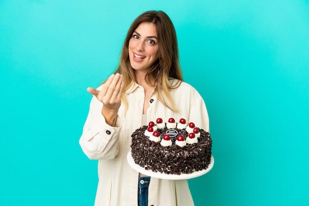 手で来るように誘う青い背景で隔離のバースデーケーキを保持している白人女性。あなたが来て幸せ