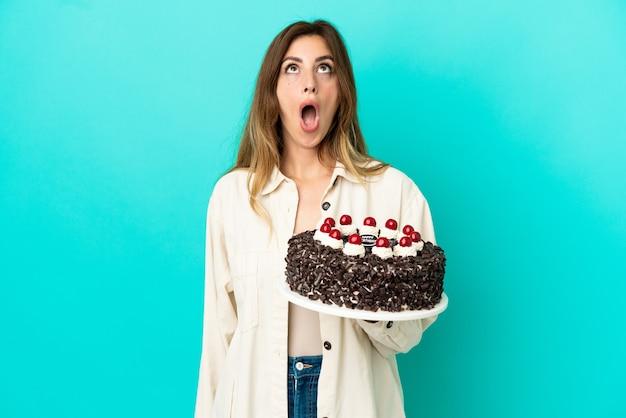 見上げると驚きの表情で青い背景に分離されたバースデーケーキを保持している白人女性