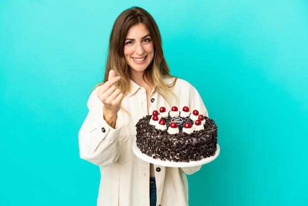 お金のジェスチャーを作る青い背景で隔離のバースデーケーキを保持している白人女性