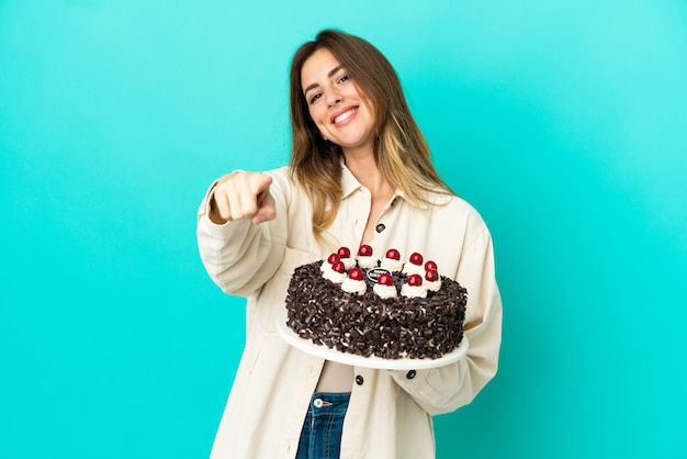 행복 한 표정으로 앞을 가리키는 파란색 배경에 고립 된 생일 케이크를 들고 백인 여자