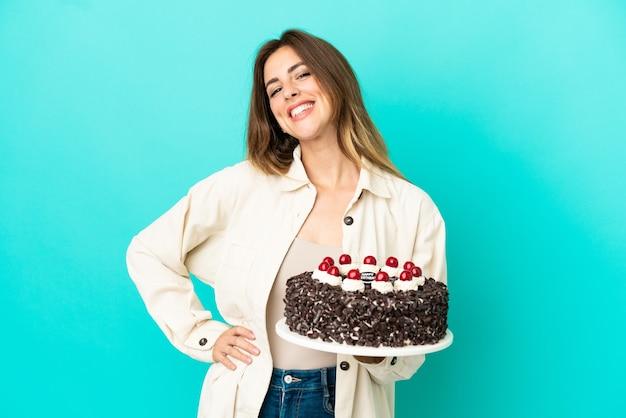 腰に腕と笑顔でポーズをとって青い背景で隔離の誕生日ケーキを保持している白人女性
