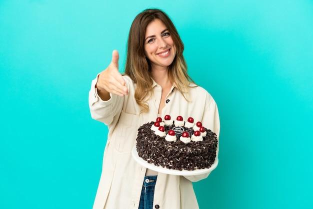 좋은 거래를 닫기 위해 악수 파란색 배경에 고립 된 생일 케이크를 들고 백인 여자