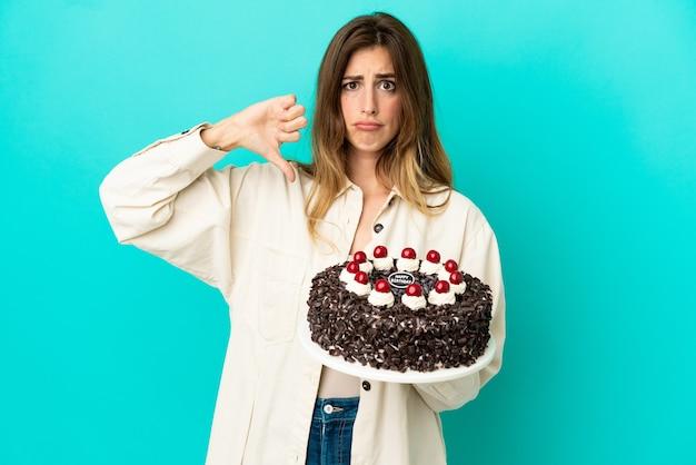 否定的な表現で親指を示す青い背景で隔離の誕生日ケーキを保持している白人女性