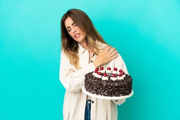 Кавказская женщина держит праздничный торт на синем фоне страдает от боли в плече из-за того, что приложила усилие