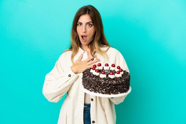 Кавказская женщина, держащая праздничный торт на синем фоне, удивлена и шокирована, глядя вправо