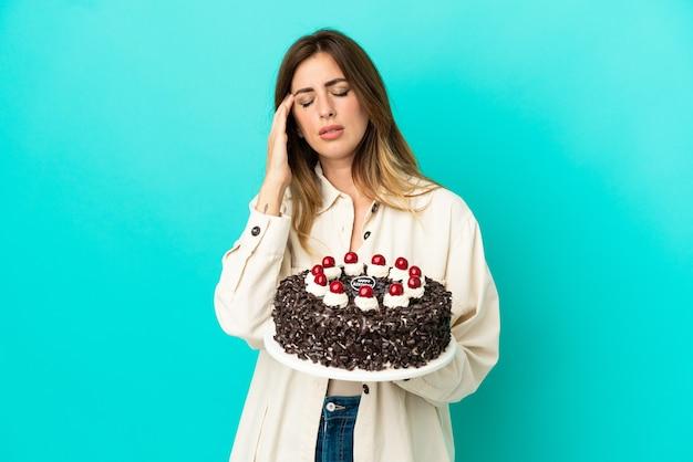 Кавказская женщина держит торт ко дню рождения, изолированные на синем фоне с головной болью