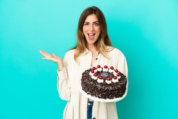 ショックを受けた顔の表情で青い背景に分離されたバースデーケーキを保持している白人女性