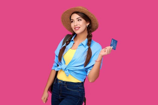 ピンクの背景で隔離のクレジットカードを保持している白人女性。オンラインショッピング、eコマース、インターネットバンキング、お金を使う、人生の概念を楽しむ