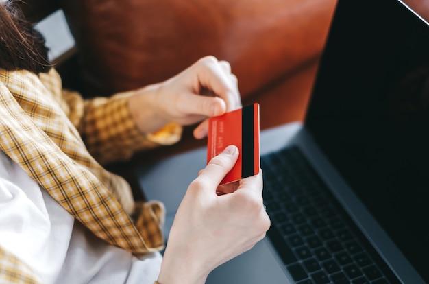 クレジットカードを持って、ラップトップコンピューターを使用してオンラインショッピングをしている白人女性。