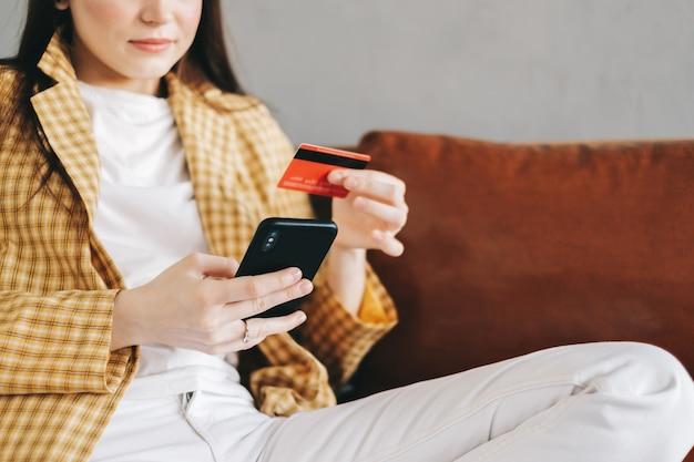クレジットカードを持って、スマートフォンを使用してオンラインショッピングをしている白人女性。
