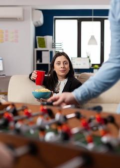 楽しい娯楽のためにフーズボールテーブルサッカーゲームサッカーを見て仕事の後にビールとチップスのカップを保持している白人女性。パーティーでお酒を飲む幸せな労働者