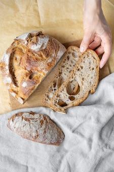 Кавказская женщина, держащая свежий хлеб из духовки, выпечка домашнего хлеба, вкусные и натуральные продукты на закваске, выпечка здоровой пищи, выпечка чиабатта