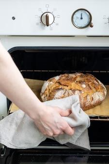 自家製パンを焼くオーブンから焼きたてのパンを保持している白人女性