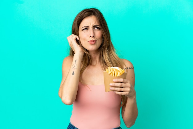 Caucasian woman holding fried chips isolated on blue background frustrated and covering ears