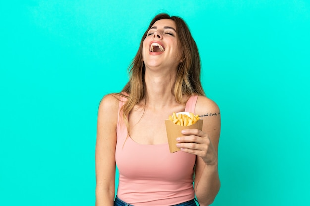Caucasian woman holding fried chips isolated on blue background laughing