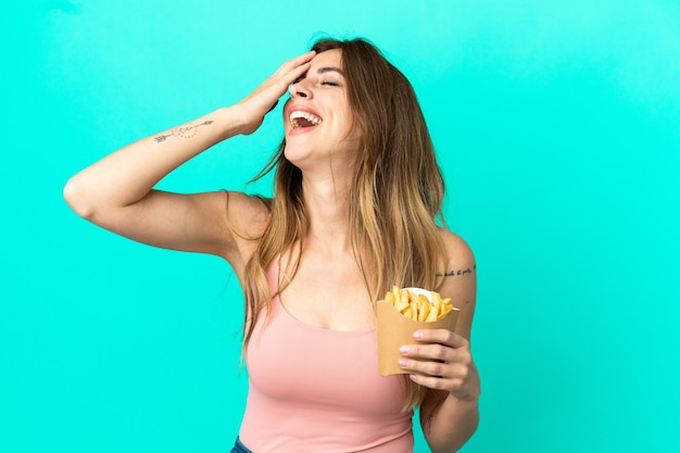Caucasian woman holding fried chips isolated on blue background smiling a lot