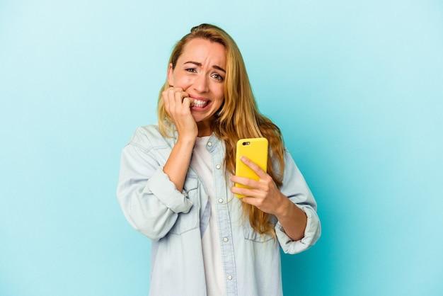 파란색 배경에 격리된 휴대전화를 들고 있는 백인 여성은 손톱을 물어뜯고 긴장하고 매우 불안해합니다.