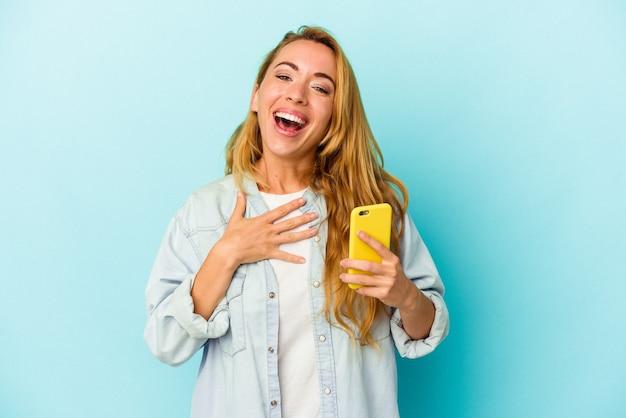 青い背景で隔離の携帯電話を保持している白人女性は、胸に手を置いて大声で笑います。