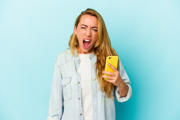 Кавказская женщина, держащая мобильный телефон, изолирована на синем фоне, кричала очень сердито и агрессивно.