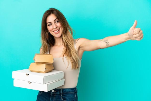 Кавказская женщина, держащая пиццу и гамбургер, изолированные на синем фоне, показывает палец вверх жестом