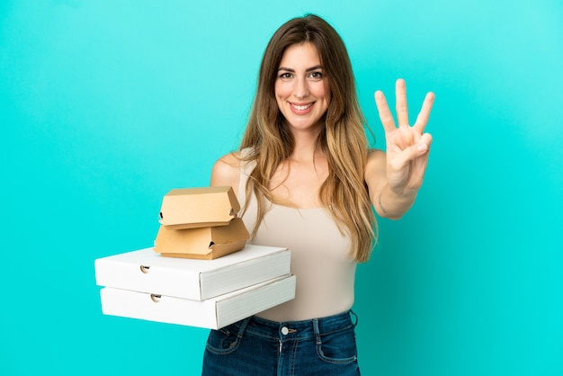 幸せな青い背景で隔離のピザとハンバーガーを保持し、指で3を数える白人女性