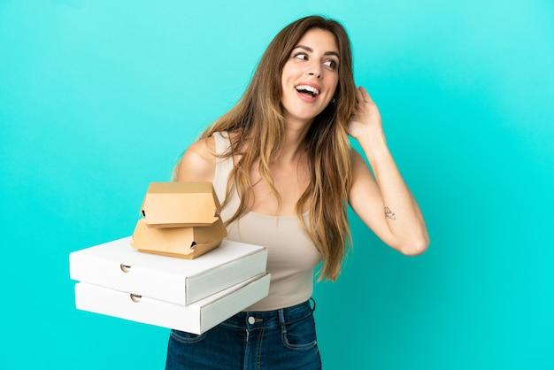 耳に手を置くことによって何かを聞いて青い背景で隔離のピザとハンバーガーを保持している白人女性
