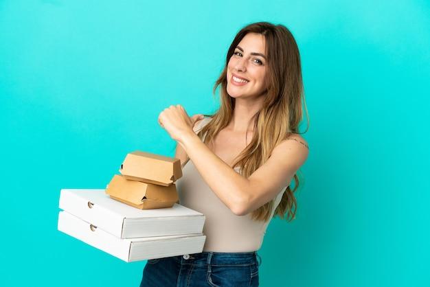 誇りと自己満足の青い背景に分離されたピザとハンバーガーを保持している白人女性