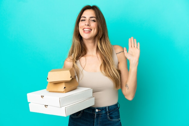 파란색 배경에 격리된 피자와 햄버거를 들고 행복한 표정으로 손으로 경례하는 백인 여성