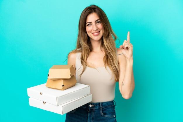 파란색 배경에 격리된 피자와 버거를 들고 있는 백인 여성이 최고라는 표시로 손가락을 들어올리고 있다
