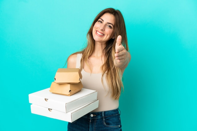 Caucasian woman holding pizzas and burger isolated on blue background shaking hands for closing a good deal