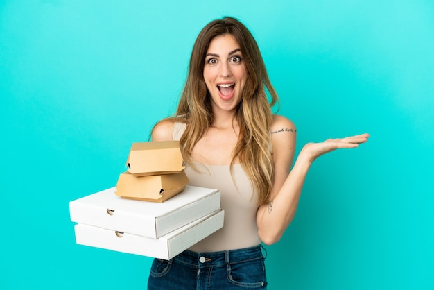 Caucasian woman holding pizzas and burger isolated on blue background with shocked facial expression