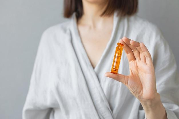 Кавказская женщина держит в руке ампулы витаминов для волос и кожи