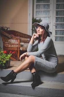 家の正面玄関につながる階段でポーズをとって灰色の帽子と黒の背の高いブーツの白人女性