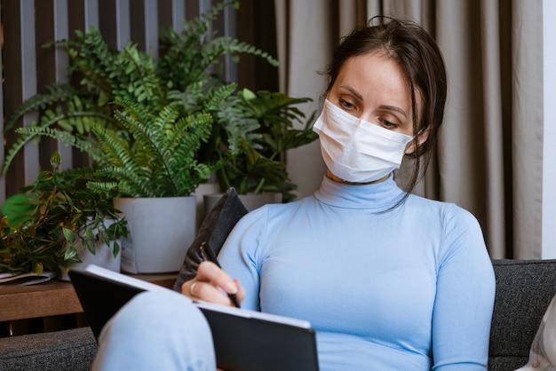보호 마스크에 백인 여자 잠겨있는 표정으로 그녀의 손에 노트북과 함께 소파에 앉아 씁니다