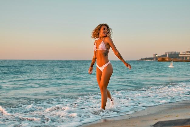 ビキニ水着の白人女性が波の音を楽しみながら日の出のビーチを散歩します。