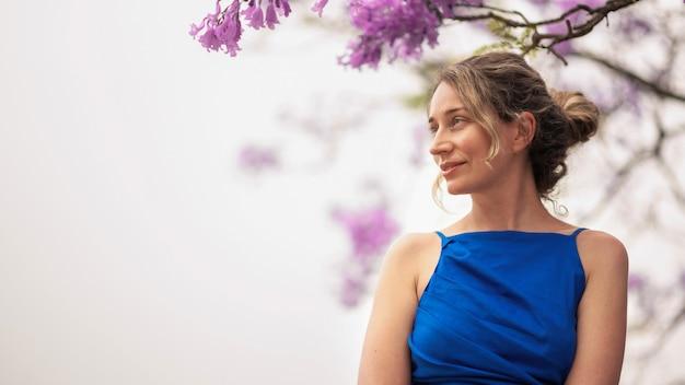 Кавказская женщина в голубом платье, розовые цветы дерева в барселоне, испания