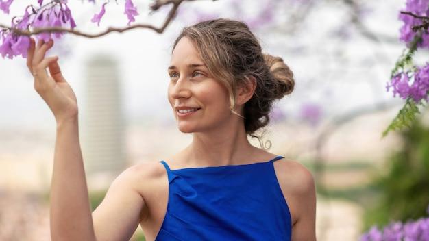 Кавказская женщина в голубом платье трогательно розовые цветы дерева в барселоне, испания