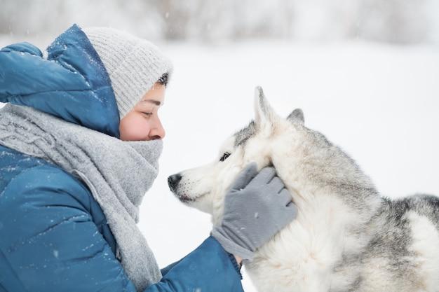 青いジャケットを着た白人女性は、冬に雪に覆われたシベリアンハスキーの顔を保持します。肖像画をクローズアップ。犬。