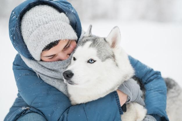 青いジャケットを着た白人女性は、冬に雪に覆われたシベリアンハスキーを抱擁します。肖像画をクローズアップ。犬。