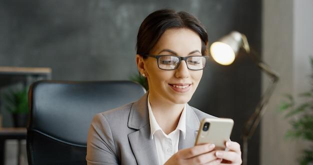 インターネットで購入して支払うメガネの白人女性。屋内。モバイル決済。