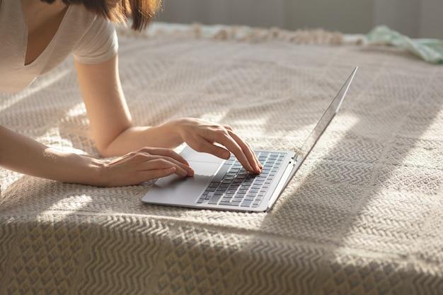 Кавказская женщина в домашнем офисе, набрав на ноутбуке, лежа на кровати в солнечный день