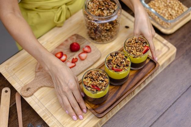 キッチンの白人女性がマンゴージャムでチアプリンを作っています。アーモンドミルク、チアシード、ココア、マンゴージャム、グラノーラでできたデザート。