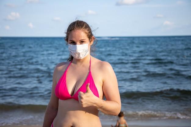 Кавказская женщина в медицинской маске и купальнике смотрит в камеру и показывает палец вверх на пляже