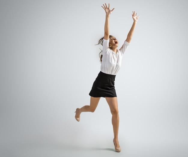 회색 벽에 고립 된 공을 잡는 사무실 옷에 백인 여자