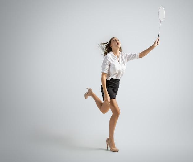 オフィスの服を着た白人女性は灰色の壁に分離されたバドミントンを再生します