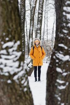 自然の木々の真ん中にある冬の公園を歩いて、散歩と冬の風景と静寂を楽しんでいるオレンジ色のジャケットを着た白人女性