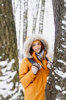 木の真ん中にある冬の公園を歩くオレンジ色のジャケットを着た白人女性、散歩と冬の風景を楽しむ自然の中で女性の肖像画