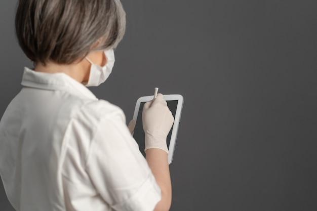 デジタルタブレットを使用して防護服の白人女性。白髪の医者は電子メモ帳で動作します。ショットを閉じる。背面または側面図。着色画像